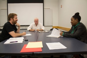 Two of the remaining graduate journalism students Nick Scott (left) and Ashley Williams (right), hold a class discussion with Professor Charles Madigan (center). Photo by: Quinton R. Arthur