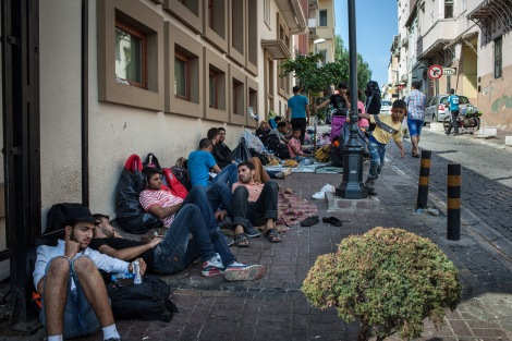 Syrians sit on a sidewalk where they have been sleeping in Izmir, Turkey, while they wait to attempt reach Greece by boat. Photo Courtesy by: Alice Martins/McClatchy/TNS