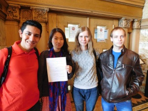 Olya Prohorova and other international students stand in from of the international program's office holding up the petition they started to change the health care policy. Photo by: Megan Schuller